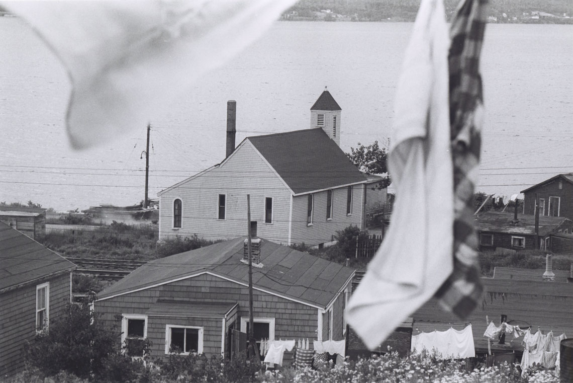 Rear view of Seaview African United Baptist Church, with Africville houses and laundry flapping in the breeze in the foreground