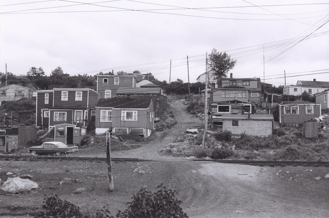 Africville houses on either side of a hillside lane, seen from the opposite side of the railroad tracks