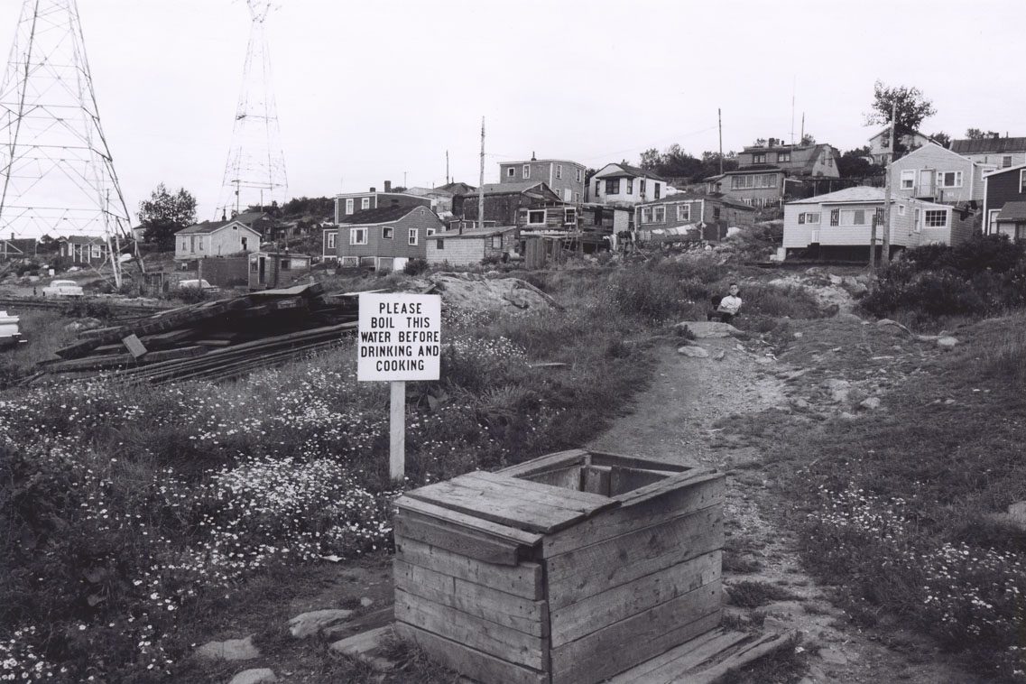 About 15 Africville houses, with a well and nearby sign reading,