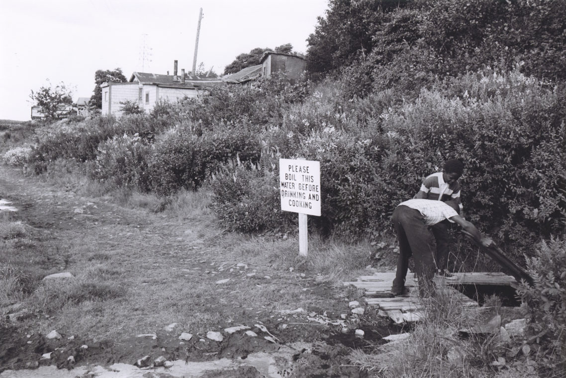 Two boys lifting the cover of a well, Africville, with nearby sign reading,