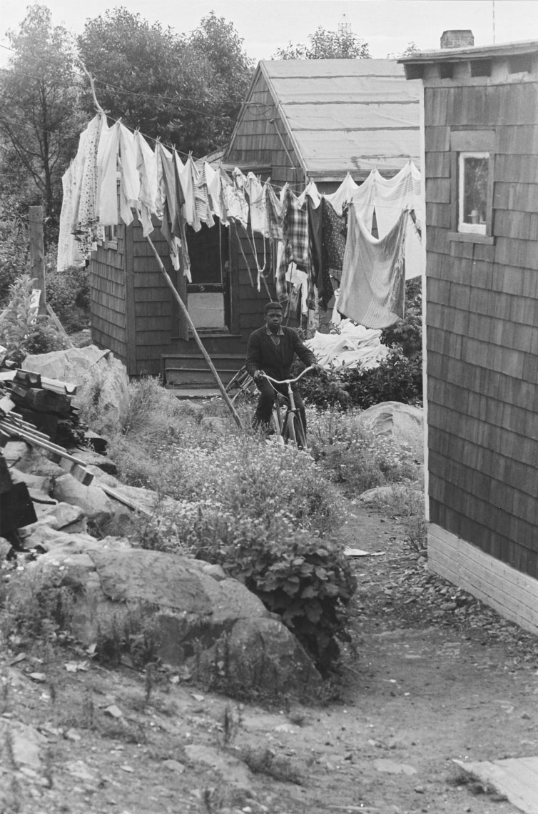 Africville backyard scene, featuring a boy with his bicycle and a full clothesline of laundry  behind him