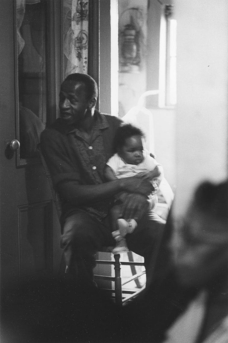 Scene shot from a doorway in an Africville house, showing a young man with a baby seated on his lap