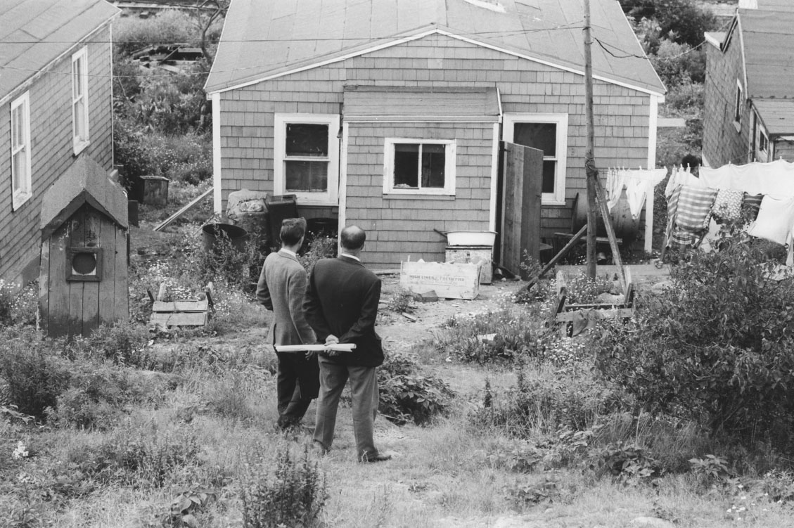 Two Halifax city officials, one holding a rolled plan of Africville, outside an Africville house, prior to demolition of the community