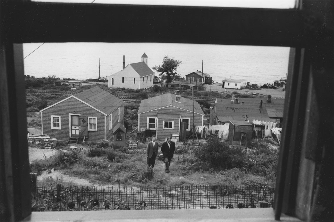 Two Halifax city officials walking up an Africville path, with several houses behind them and Seaview Baptist Church in the background