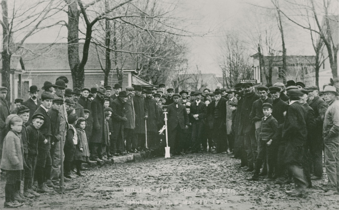 Turning first sod for water (3rd man to left of shovel – Capt. Bob Lawrence (shoe store); shovel – Delancey Falkner (mayor); to right of shovel – George D. Comstock (Walter – little boy between); man with moustache 5th from right – John Woolaver; man with gray overcoat 3rd to right of shovel – Dr. Margeson; 3rd little boy from left – Clarence Riley; 8th letter girl from left – Beulah Coyle; behind Delaney – Billy Pearson