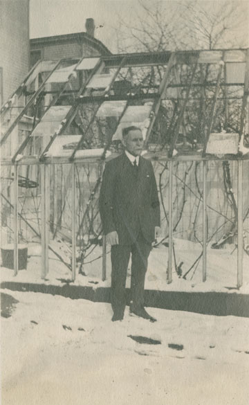 Father Charles E. Creighton in front of greenhouse after Halifax Explosion, Portland St., Dartmouth