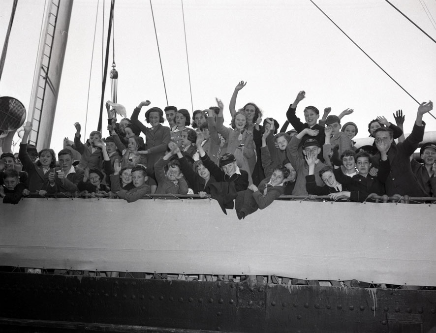 Several shots of a large group of people, including British evacuee children
