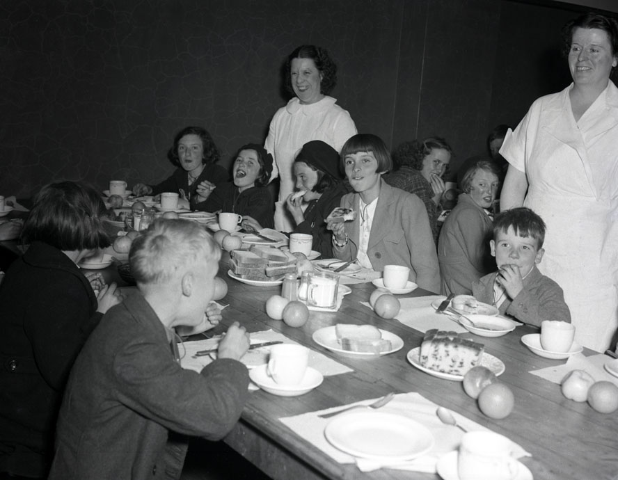 Several shots of a large group of people, including British evacuee children, eating lunch Ocean Terminals