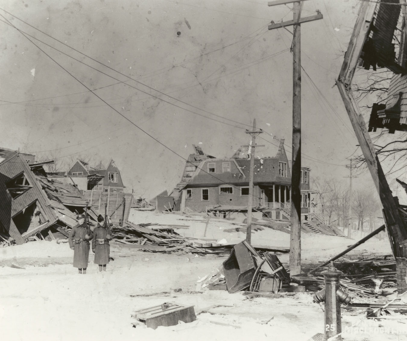 Soldiers standing guard in the midst of the devastation on Kaye Street east of Gottingen Street, Halifax