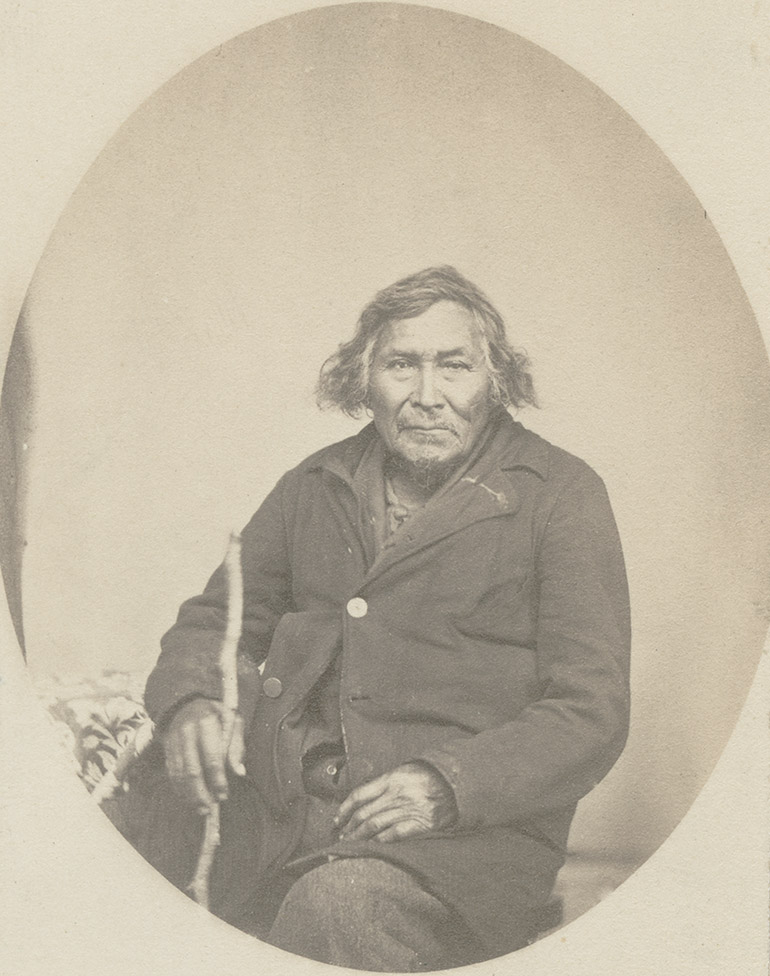 Mi'kmaq man, seated, with a walking stick