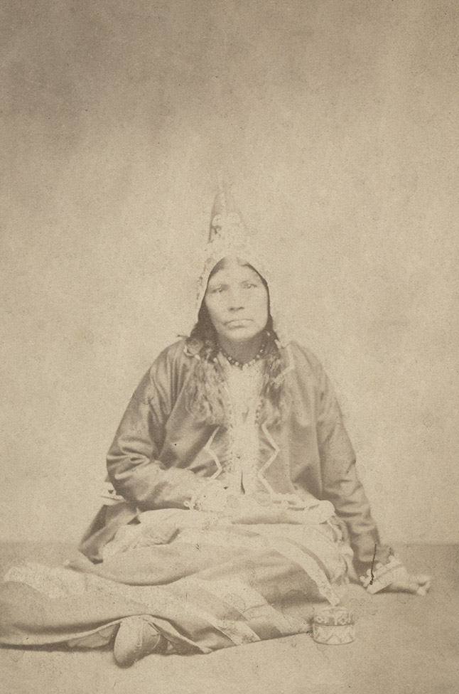 Mi'kmaq woman seated on studio floor, with quillwork canoe model and box.