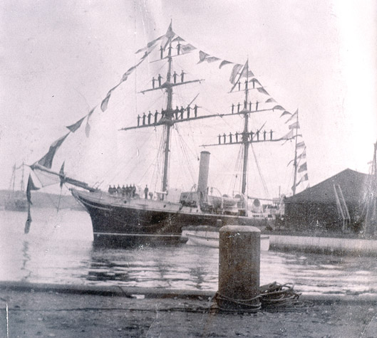 Naval ship decorated with flags and men in the rigging