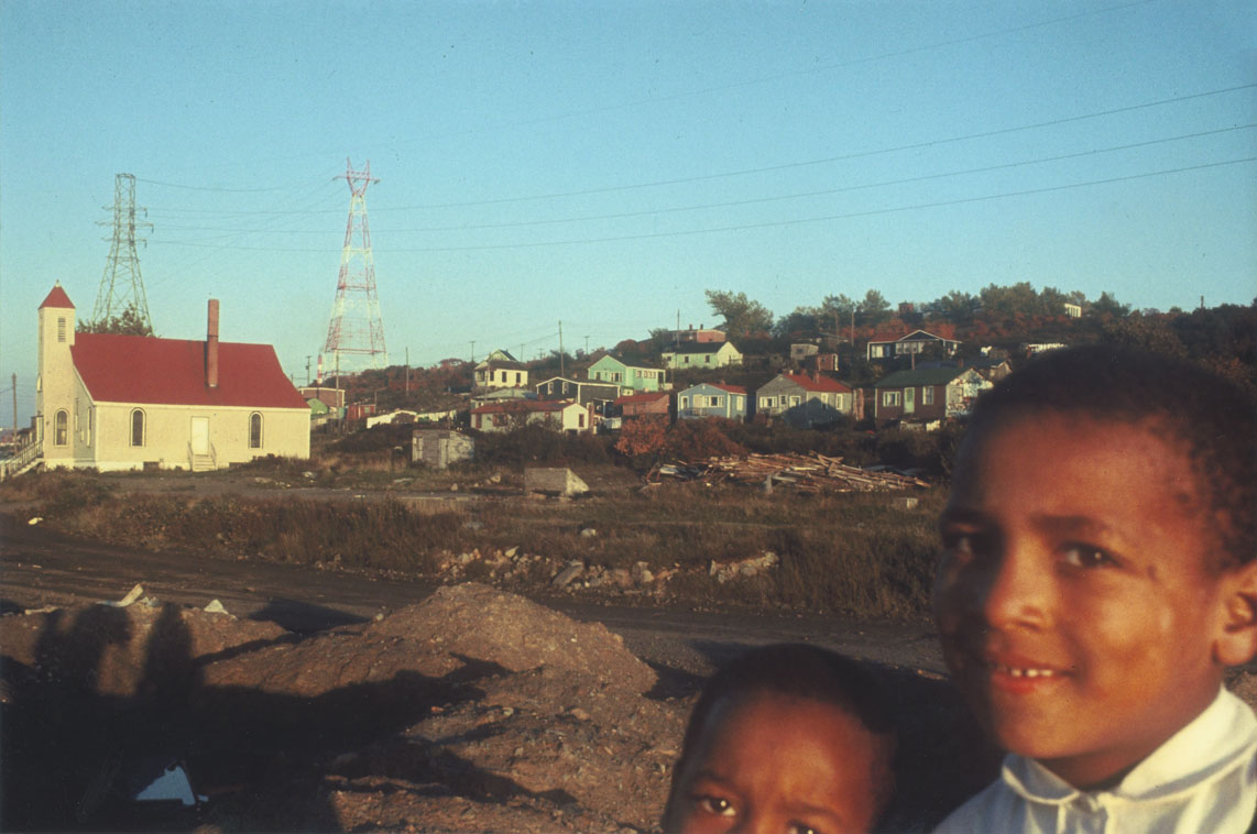 Two Africville children, with Seaview African United Baptist Church and houses behind it in the distance