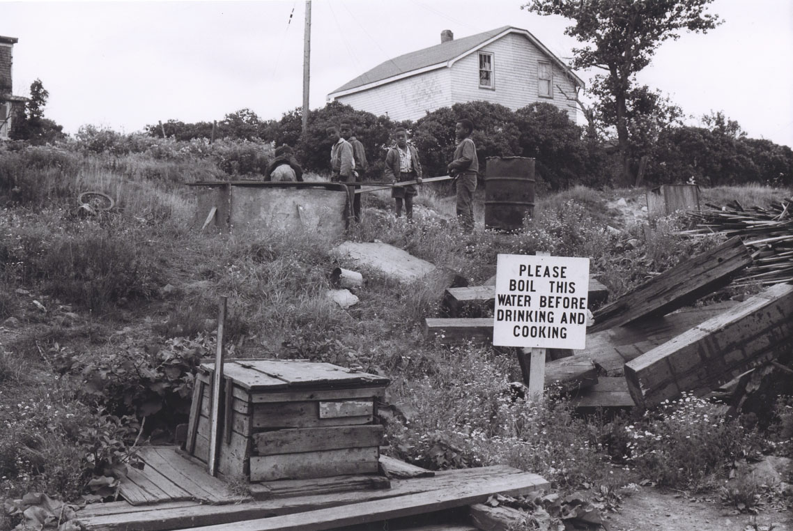 Another of Africville's wells with a sign reading,