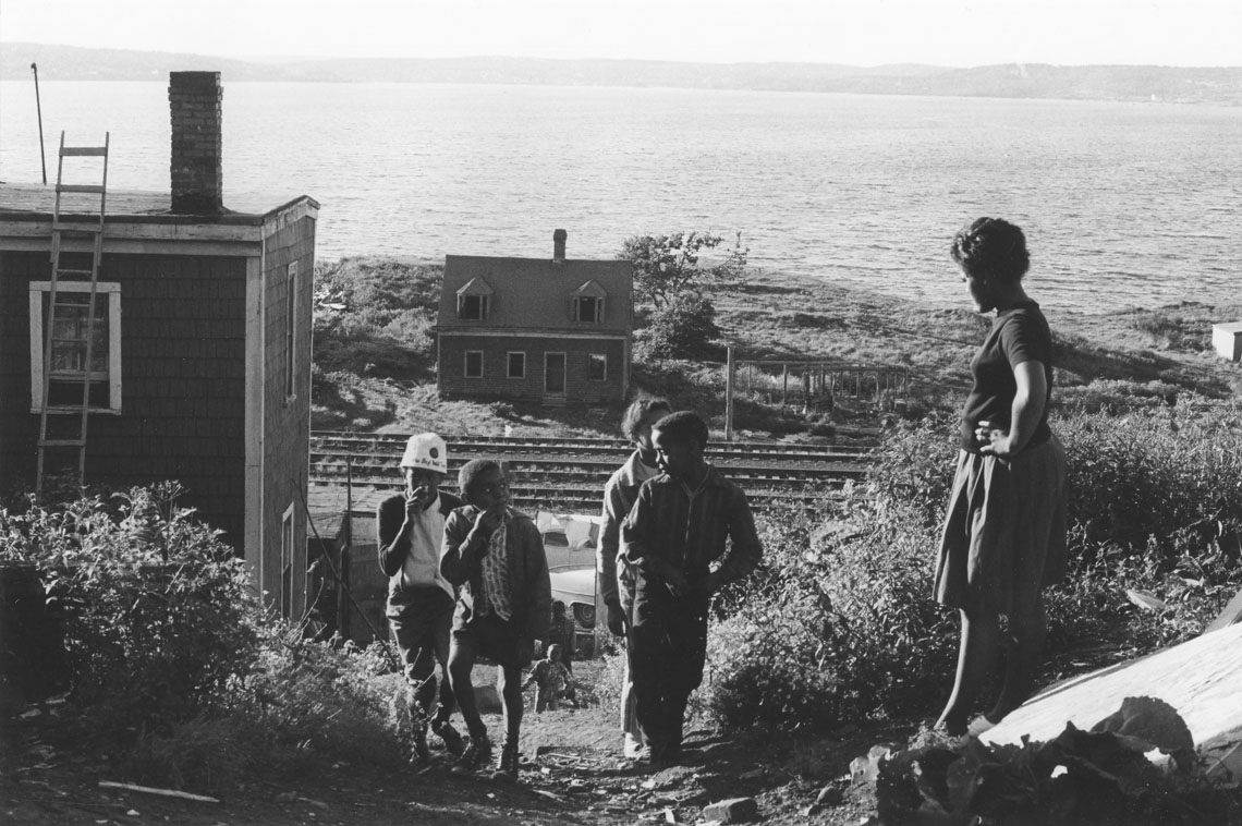 africville : Woman, hands on hips, watching a group of children climbing a path, Africville