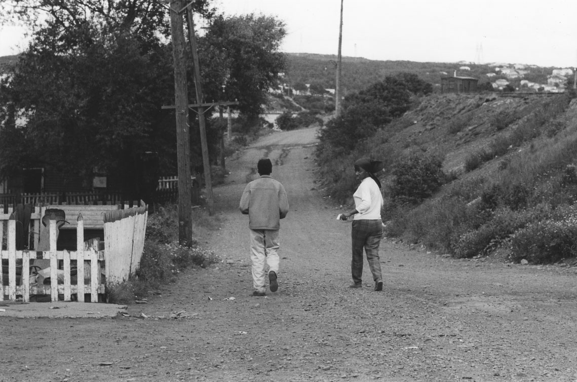 africville : Two young people walking along an unpaved street, Africville