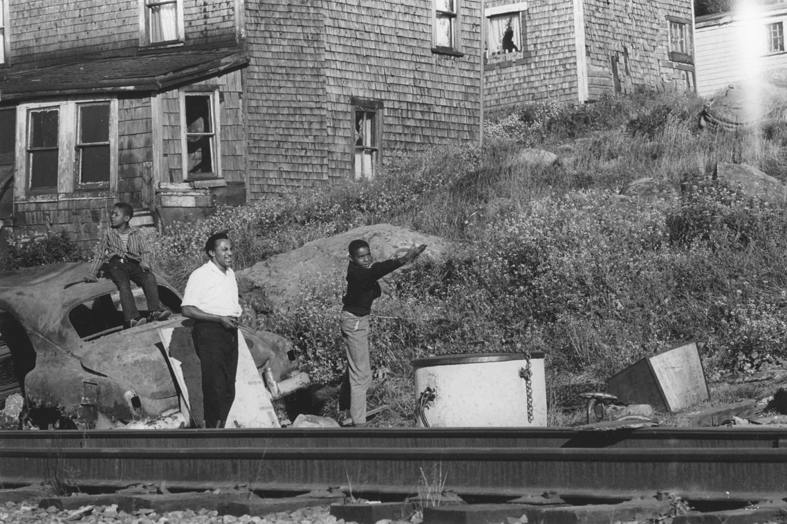 africville : Young men playing horseshoes, seen from the opposite side of the railway tracks, Africville.