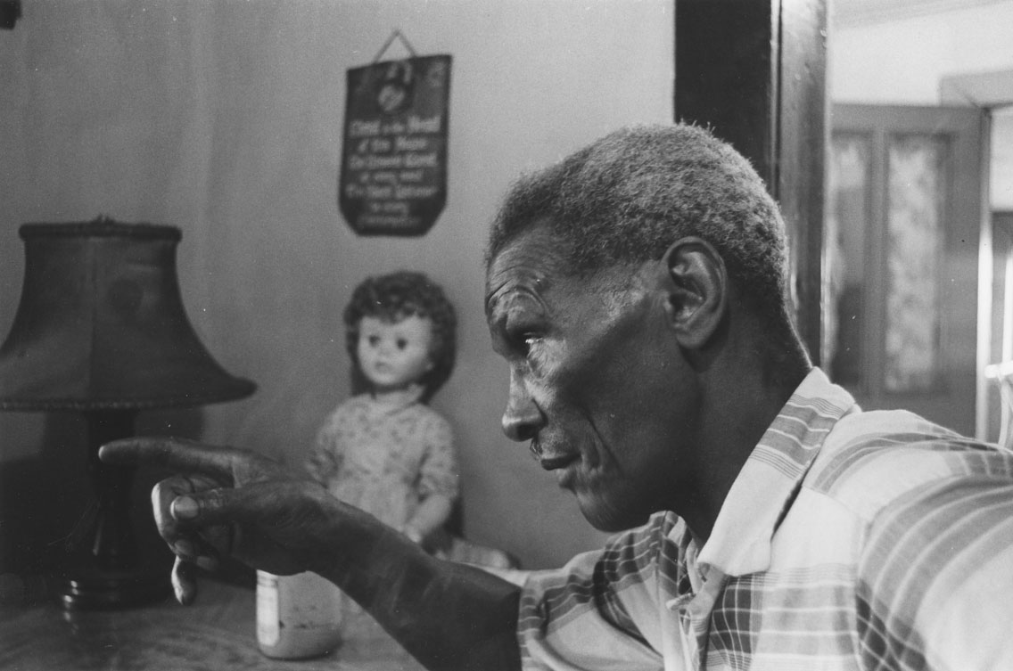 africville : Man making a point during a discussion at dining room table, Africville