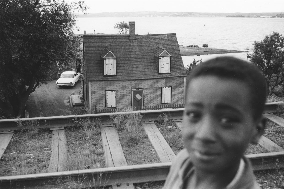 africville : Young boy, with Ralph Jones house, Africville, boarded up prior to demolition, in the background