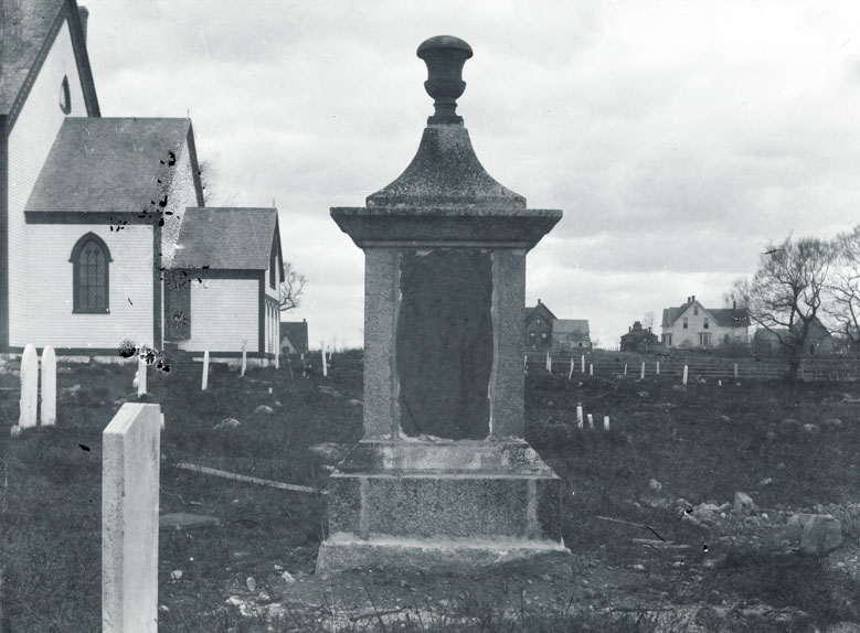 Tombstone in Anglican graveyard with back of Christ Church (Hammond Street) visible, Shelburne, N.S.