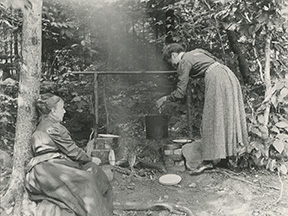 Two Women Cooking Over a Campfire