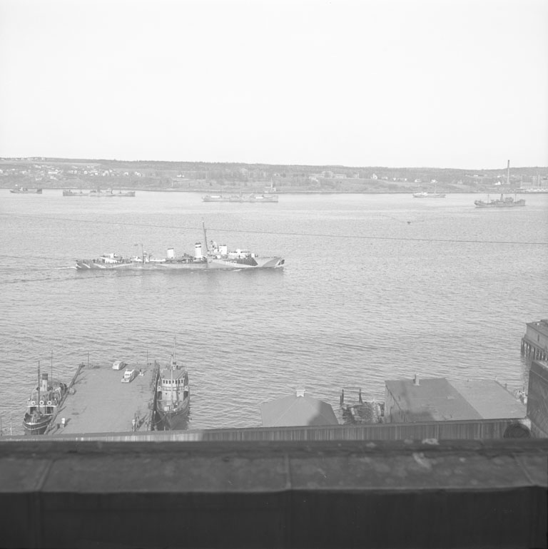 Destroyer H-60, HMCS <i>Ottawa</i> goes out, in background are British freighters