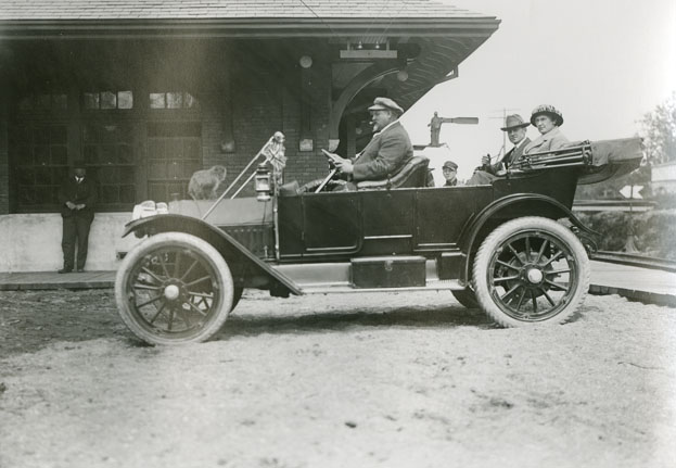 Well-Dressed Couple in a Chauffeur-Driven Automobile